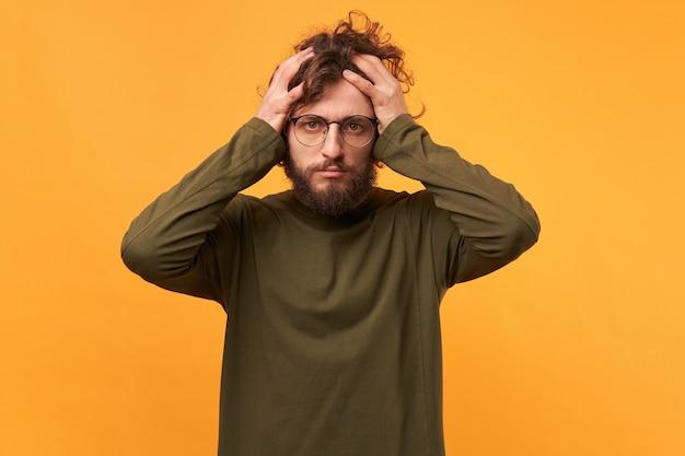 Een man met een bril met een baard naar zijn hoofd geklemd ziet er verdrietig uit, kwam in wanhopige situaties terecht Gratis Foto