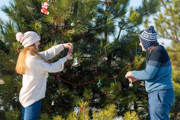Een man met een meisje siert een groene kerstboom op een straat in de winter in het bos met decoratief speelgoed en slingers, kerstboomversieringen Premium Foto