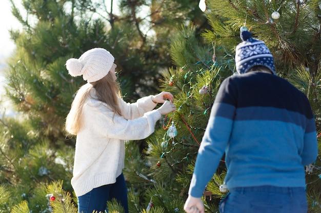 Een man met een meisje siert een groene kerstboom op straat in de winter in het bos met decoratief speelgoed en slingers. kerstboomdecoraties Premium Foto