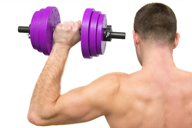 Een man met een mooi lichaam houdt zich bezig met fitness. het uitzicht vanaf de achterkant. geïsoleerd Premium Foto