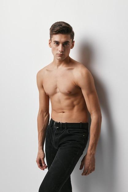 Een man met een naakte torso en een broek in een licht bijgesneden beeld Premium Foto