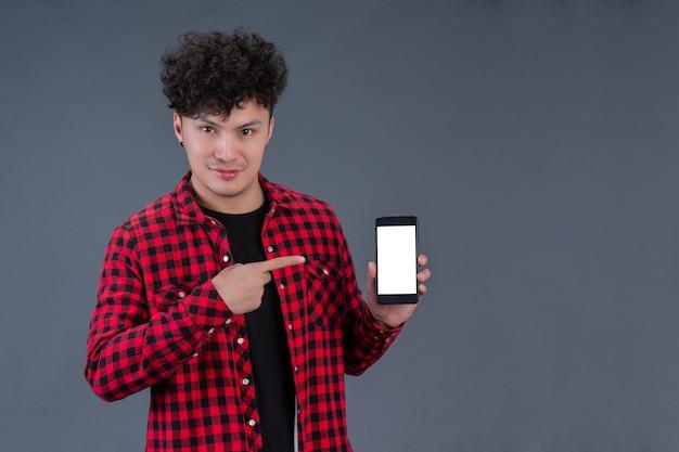 Een man met een rood geruit overhemd met een smartphone Gratis Foto