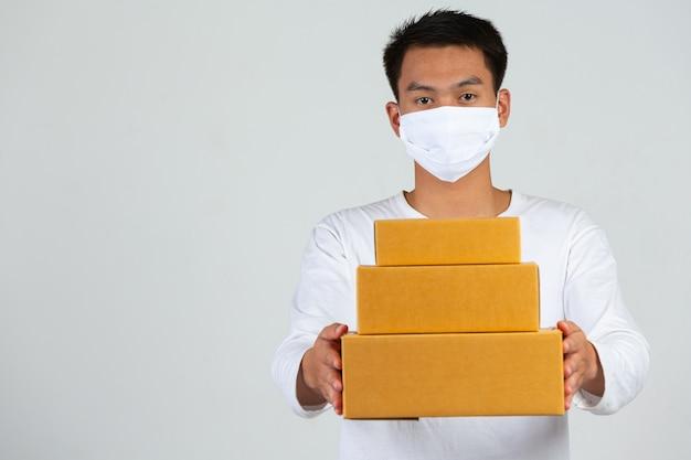 Een man met een wit t-shirt houdt een bruine brievenbus vast om dingen te bezorgen. maak gebaren en gezichtsuitdrukkingen. Gratis Foto