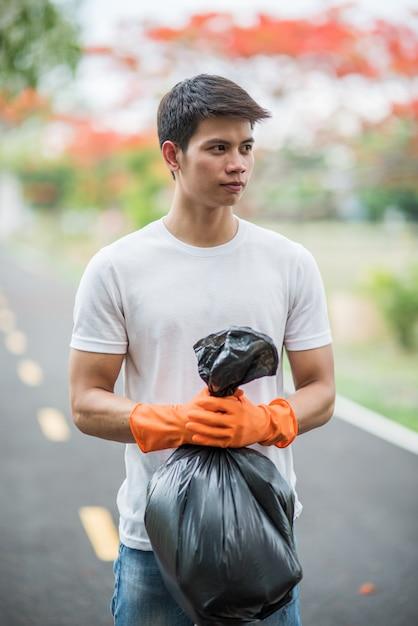 Een man met oranje handschoenen die vuilnis in een zwarte zak verzamelen. Gratis Foto