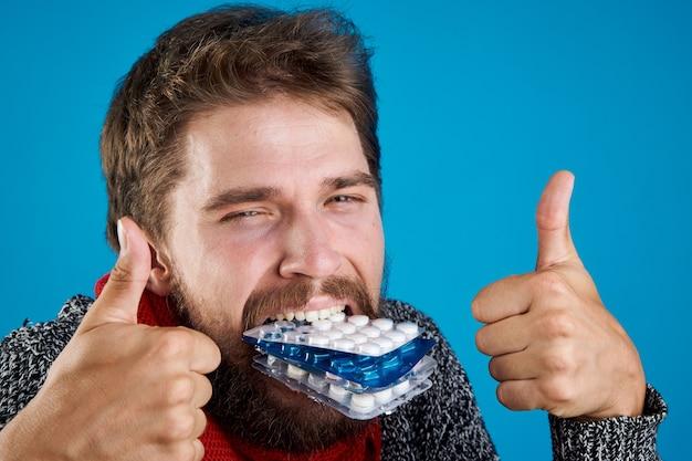 Een man met pillen in zijn tanden gebaren met zijn handen gezondheidsproblemen warme kleren rode sjaal Premium Foto