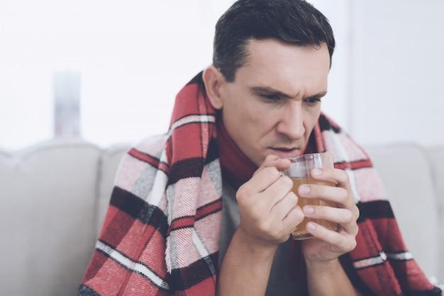 Een man met verkoudheid zit op de bank met sneez. Premium Foto