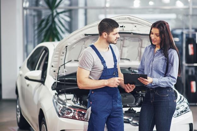 Een man monteur en vrouw klant bespreken reparaties aan haar voertuig Gratis Foto