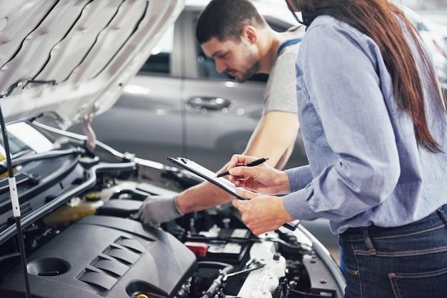 Een man monteur en vrouw klant kijken naar de motorkap en bespreken reparaties Gratis Foto