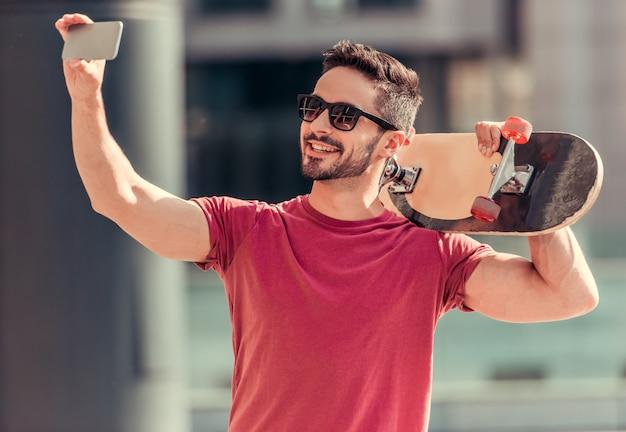 Een man neemt een selfie met een schaats in zijn handen. Premium Foto