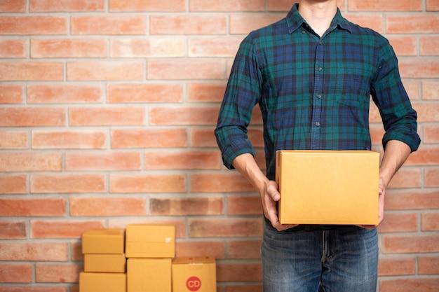 Een man ondernemer ondernemer mkb bedrijf is een verpakking om zijn klant te sturen Premium Foto