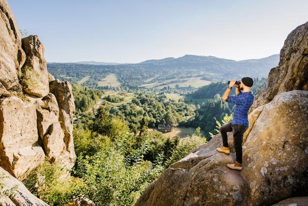 Een man reiziger staande op de top van de berg en kijkend in de verrekijker aan de horizon Premium Foto