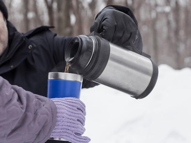 Een man schenkt thee aan een vrouw uit een thermoskan in een thermosbeker om te drinken en op te warmen. Premium Foto