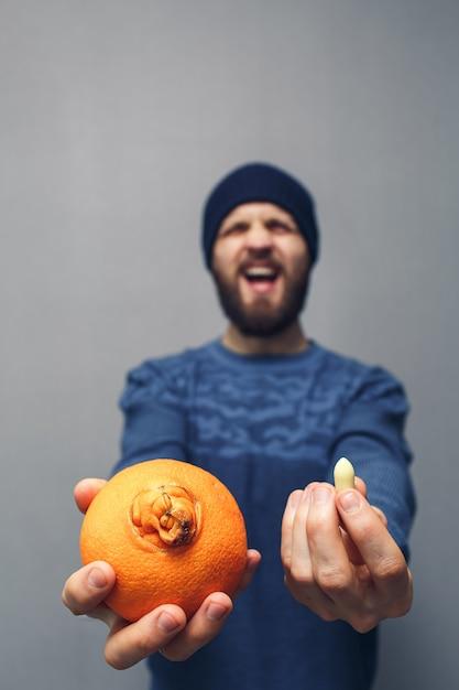 Een man schreeuwt in problemen vanwege aambeien. een bebaarde man heeft een sinaasappel en een zetpil voor aambeien in zijn handen. aambeien concept. Premium Foto