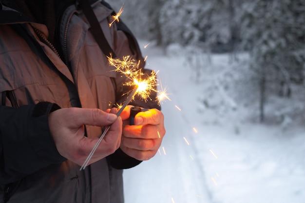 Een man steekt sterretjes aan in een winterbos. Premium Foto