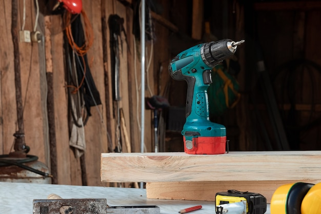 Een man timmerman draait een schroef in een boom met een elektrische schroevendraaier, mannelijke handen met een schroevendraaier close-up. Premium Foto
