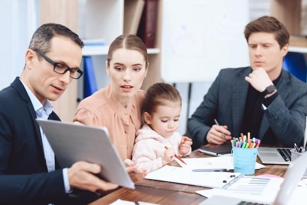 Een man toont een vrouw met een kind iets op de tablet. Premium Foto