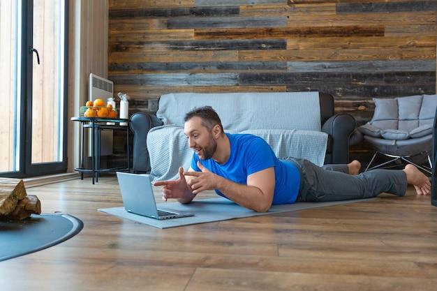 Een man van middelbare leeftijd tijdens een online videogesprek. hij ligt op de grond terwijl hij voor een laptopmonitor staat. Premium Foto