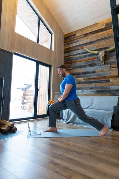 Een man warmt zijn spieren op voordat hij gaat trainen. online training met een tutorial van internet. gezond levensstijlconcept. Premium Foto