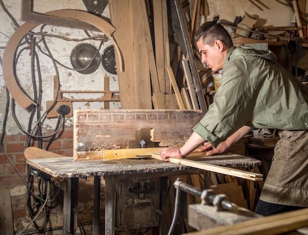 Een man werkt aan de machine met de vervaardiging van houten producten Gratis Foto