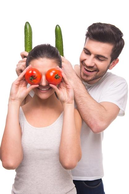 Een man zet de hoorns van een meisje met komkommers. Premium Foto