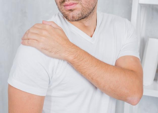 Een man zijn gewonde schouder aanraken met de hand Gratis Foto
