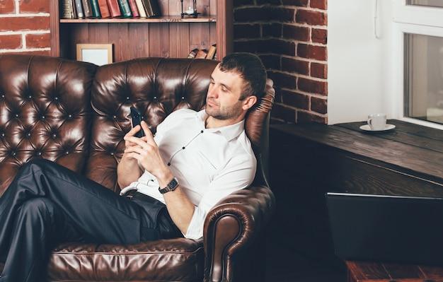 Een man zit op een comfortabele leren bank en houdt de telefoon in zijn handen. de zakenman rust van het werk achter laptop Premium Foto