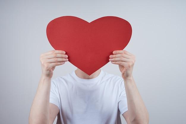 Een man zonder gezicht, een gezicht bedekt met een papieren hart Premium Foto