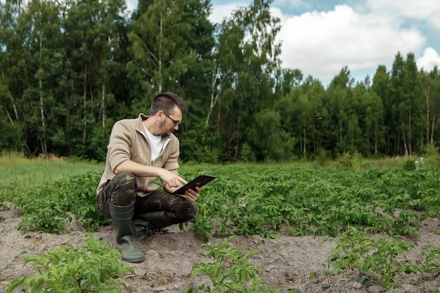 Een mannelijke boer zit in het veld en met behulp van een tablet. moderne toepassing van technologieën in landbouwactiviteiten. Premium Foto