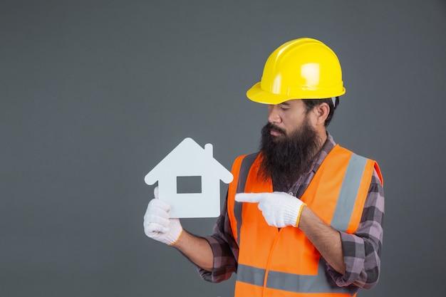 Een mannelijke ingenieur die een gele veiligheidshelm draagt die een wit huissymbool op grijs houdt. Gratis Foto