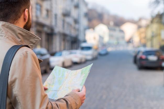 Een mannelijke kaart van de reizigersholding die in hand de manier op stadsstraat vinden Gratis Foto