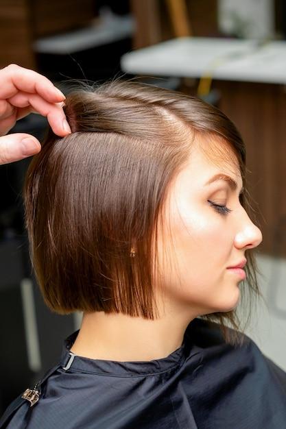 Een mannelijke kapper maakt het haar van de jonge vrouw in een schoonheidssalon recht Premium Foto