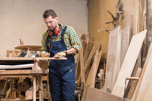 Een mannelijke timmerman die in de workshop werkt Gratis Foto