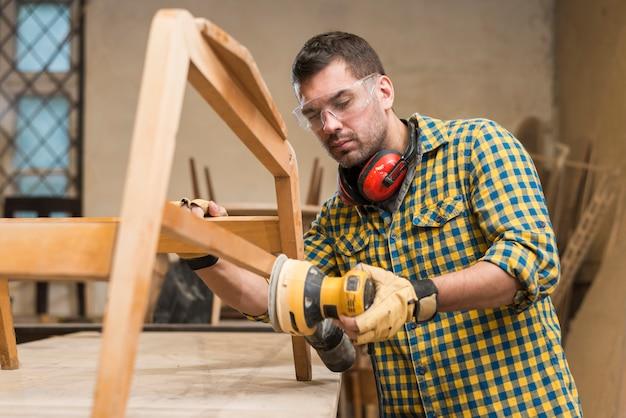 Een mannelijke timmerman die veiligheidsbril draagt die schuurmachine op meubilair in workshop met behulp van Gratis Foto