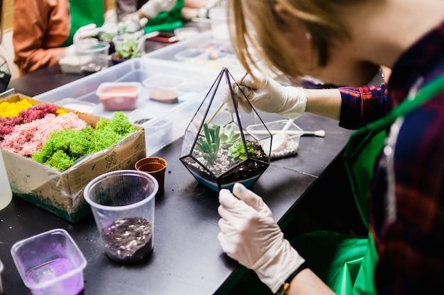 Een masterclass in het planten van cactussen en sukkulentov in de vorm van glas Premium Foto