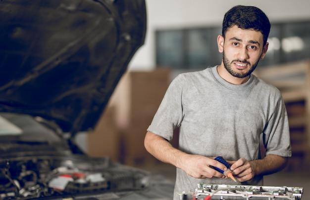 Een medebankman die de details van een auto repareert en olie toevoegt Gratis Foto