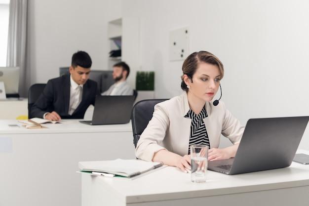 Een medewerker van een callcenter zit aan een balie in het kantoor van een groot financieel bedrijf in een strikte dresscode voor het kantoor. Premium Foto