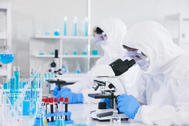 Een medische professional in een antiplaguepak is volledig beschermd tegen het virus en draagt steriele rubberen handschoenen en kijkt door de lens van een microscoop terwijl hij in een laboratorium zit. Premium Foto