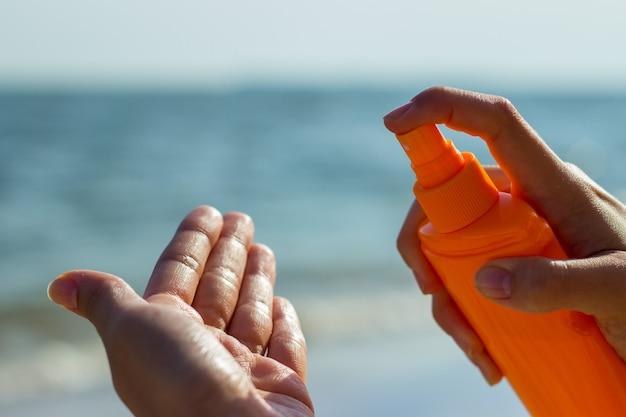 Een meisje die een fles zonnescherm houden en zonnescherm op de palm op tropische strandvakantie toepassen Premium Foto