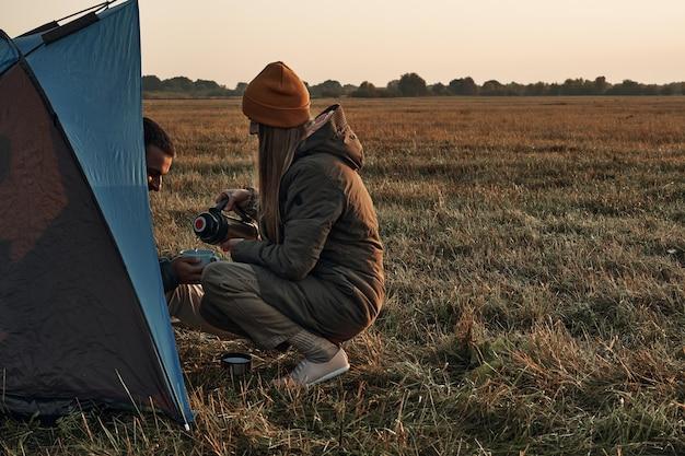 Een meisje en een jongen in een tent drinken uit een mok, herfsttijd, reizen. ze ontmoeten de dageraad in de natuur. Premium Foto