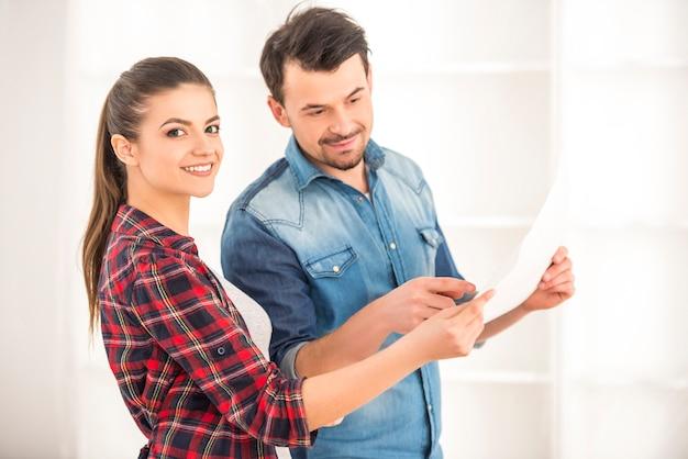 Een meisje en een man overwegen een plan voor een nieuw appartement. Premium Foto