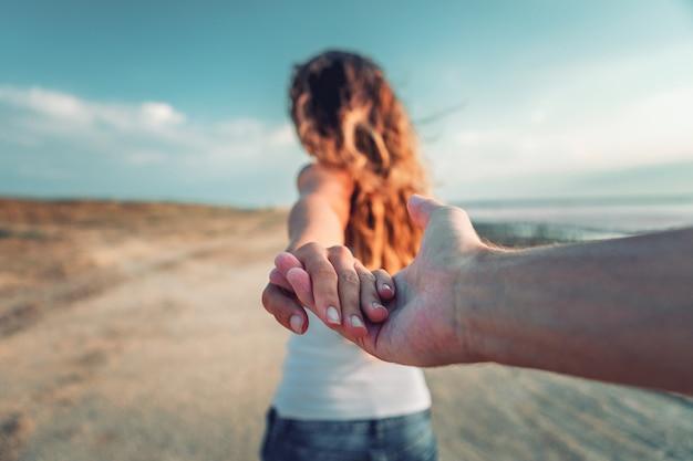 Een meisje gaat op een post met een kerel aan een hand Premium Foto