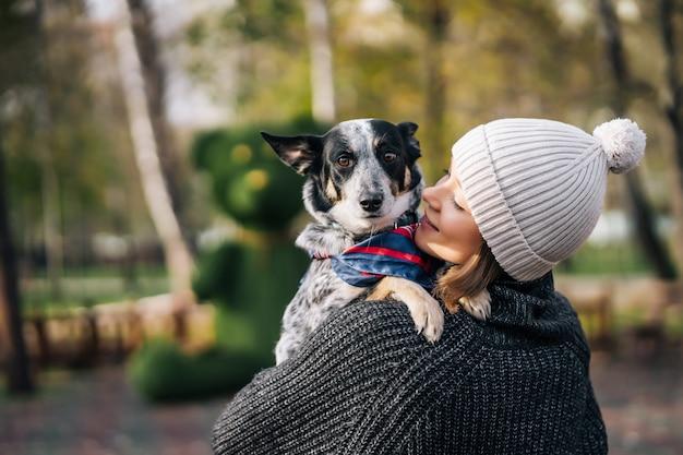 Een meisje houdt een bastaarde hond in haar armen. voor dieren zorgen. Gratis Foto