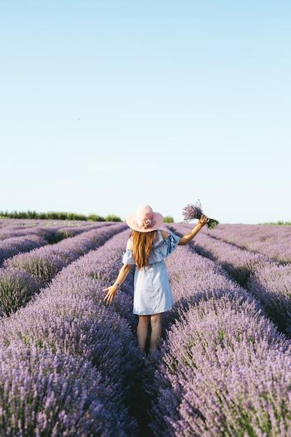 Een meisje in blauwe jurk lopen via lavendelvelden bij zonsondergang. Premium Foto