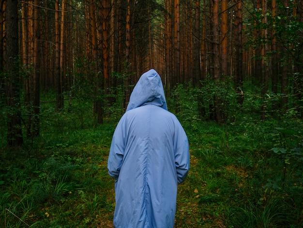 Een meisje in een blauwe regenjas staat midden in een dennenbos Premium Foto