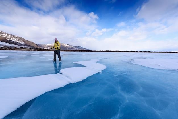Een meisje in een gele jas en schaatsen staat op het blauwe meer van het baikalmeer Premium Foto