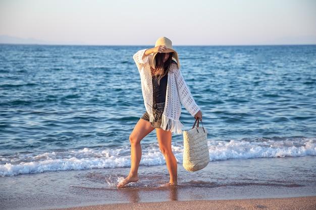 Een meisje in een grote hoed met een rieten tas loopt aan de kust. zomer vakantie concept. Gratis Foto