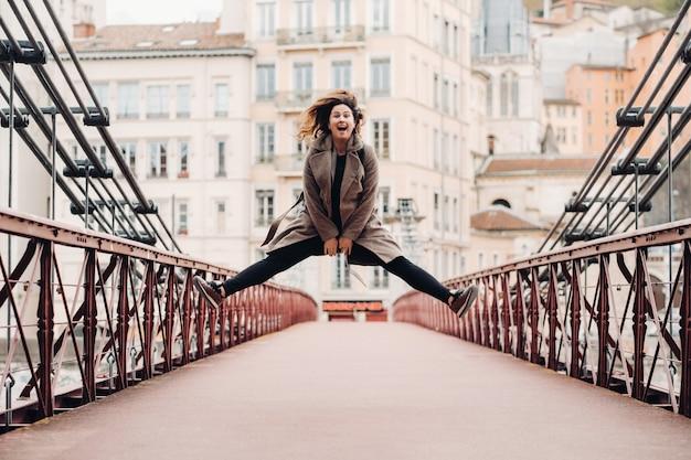 Een meisje in een jas met haar haren naar beneden springt emotioneel op een brug in de oude stad lyon. frankrijk. meisje in een jas in frankrijk. Premium Foto