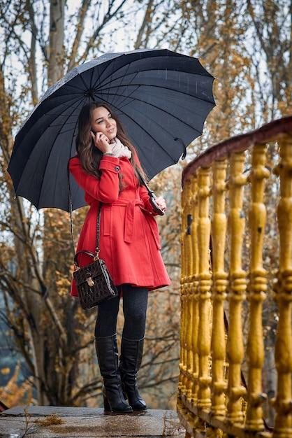 Een meisje in een rode jas onder een zwarte paraplu praat aan de telefoon Premium Foto