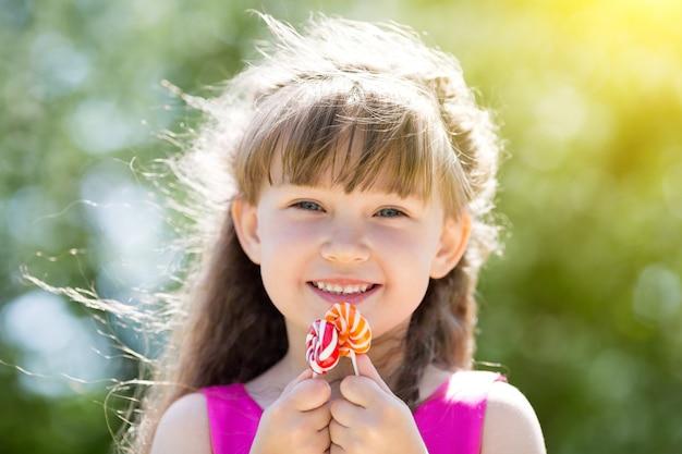 Een meisje in een rode jurk met snoepjes in haar handen. Premium Foto