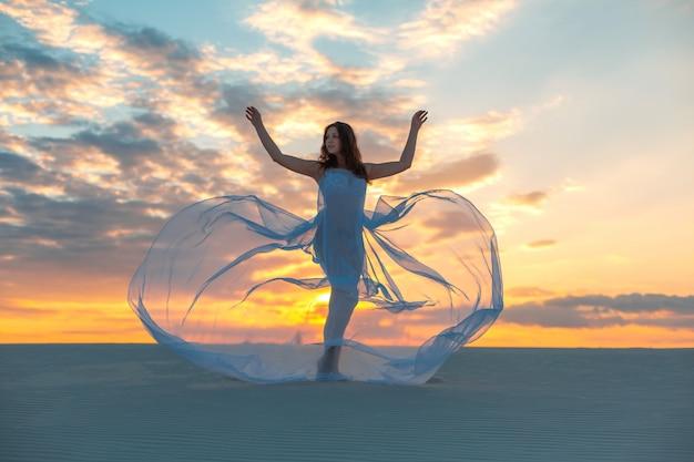 Een meisje in een vlieg witte jurk danst en poseert in de zandwoestijn bij zonsondergang Premium Foto